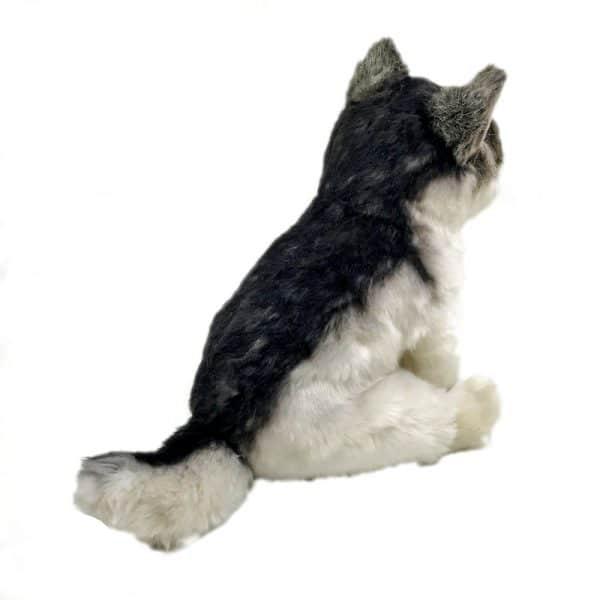 Peluche d'un loup gris assis vue de dos