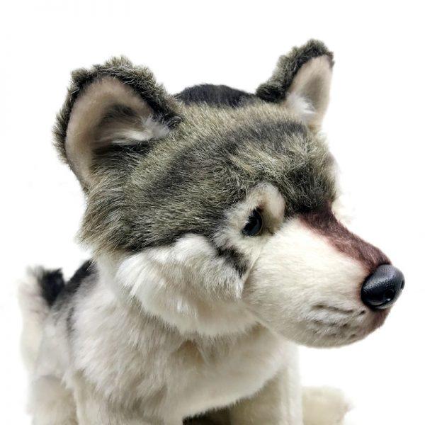 Peluche d'un loup gris assis vue de près au niveau de la tête
