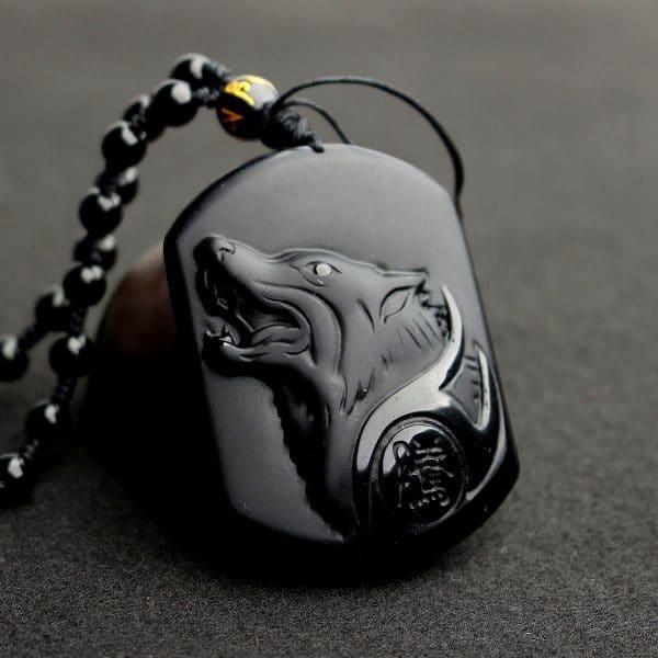 Collier Loup Obsidienne vue de pres sur un fond